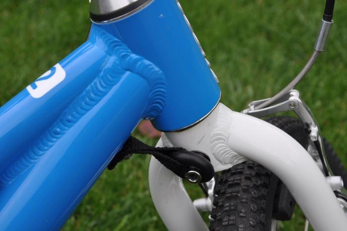 Elastyczny ogranicznik skrętu kierownicy w WOOM 2 pomaga zachować kontrolę nad rowerkiem.